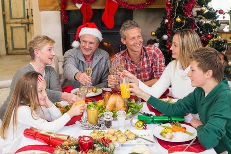 comida de navidad: Familia extensa que tuestan en la cena de Navidad en casa en la sala de estar