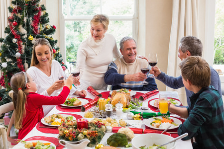 pere noel: Famille, grillage, vin rouge dans un repas de Noël à la maison dans le salon Banque d'images
