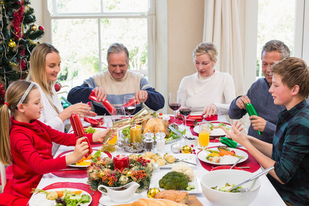 festivity: Family pulling christmas crackers at the dinner table at home in the living room Stock Photo