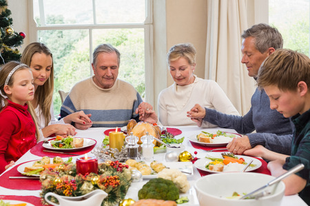 traditional christmas dinner: Extended family saying grace before christmas dinner at home in the dining room Stock Photo