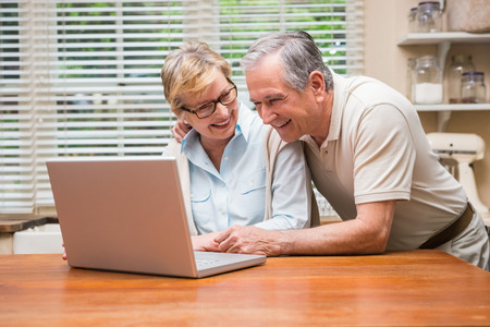 Senior couple using the laptop together at home in the kitchen photo