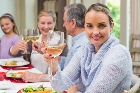 Woman smiling at camera while holding a glass of wine at home in the living room photo