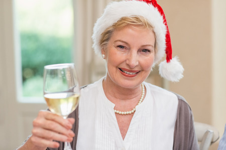 traditional christmas dinner: Smiling mature woman in santa hat toasting with white wine Stock Photo