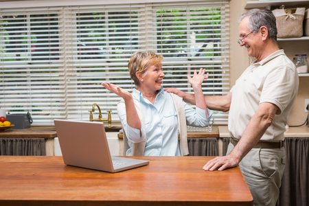 Senior couple using the laptop together at home in the kitchen Stock Photo