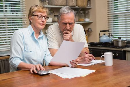 factura: Pares mayores que trabajan a cabo sus proyectos de ley en su casa en la cocina