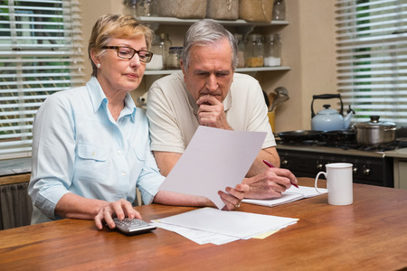 pay desk: Senior couple working out their bills at home in the kitchen