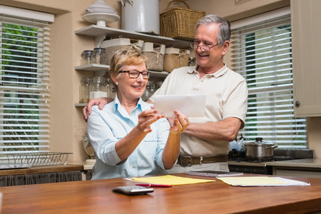figuring: Senior couple working out their bills at home in the kitchen