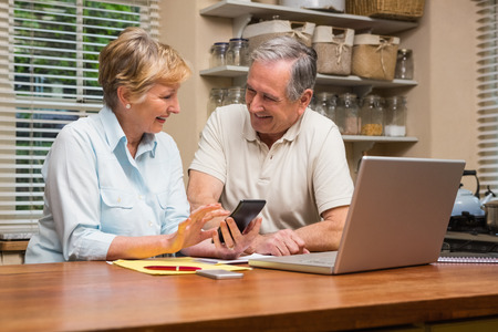 Senior couple working out their bills at home in the kitchen photo