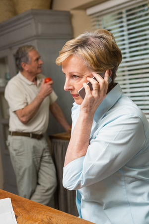 Senior woman on the phone  at home in the kitchen Stock Photo
