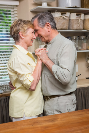 Romantic senior couple dancing together  at home in the kitchen photo