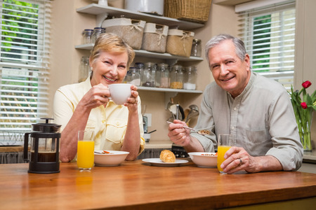 eating breakfast: Senior couple having breakfast together at home in the kitchen