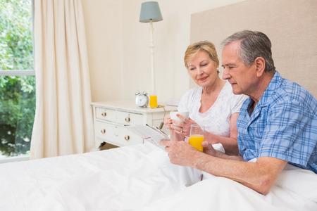 Senior couple having breakfast in bed at home in bedroom photo