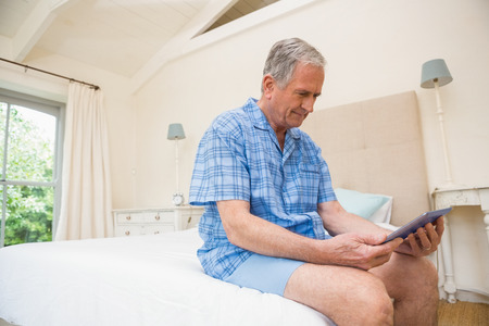 Senior man using tablet pc at home in bedroom
