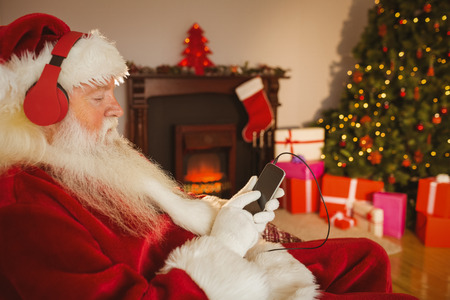 Santa claus listening music with his smartphone at home in the living room Stock Photo