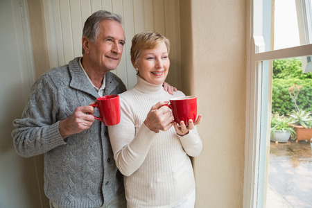 senior citizen: Senior couple holding red mugs at home in the kitchen