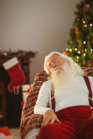 Santa claus resting on the armchair at home on the living room photo
