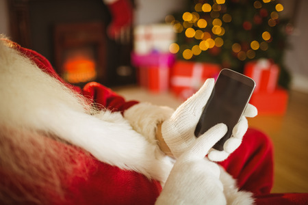 Santa claus touching a smartphone at christmas at home in the living room Stock Photo