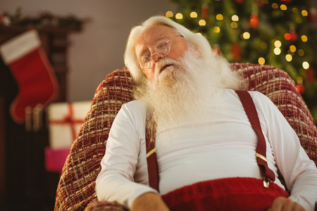 Santa claus sleeping on the armchair at home in the living room photo