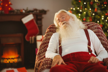 Santa claus napping on the armchair at home in the living room photo