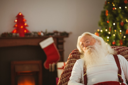 Father christmas resting on the armchair at home in the living room photo