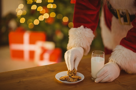 Santa picking cookie and glass of milk on the table at home 免版税图像