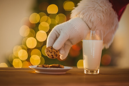 cookies: Hand of santa claus picking cookie on the table at home Stock Photo