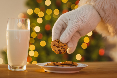 milk and cookies: Hand of santa claus picking cookie on the table at home Stock Photo