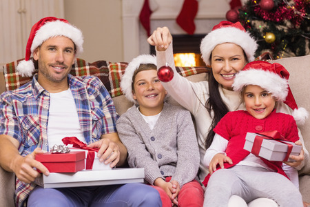 wearing santa hat: Happy family wearing santa hat on the couch at home in the living room Archivio Fotografico