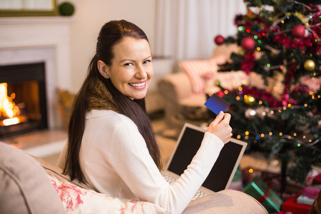 Smiling brunette shopping online with laptop at christmas at home in the living room photo