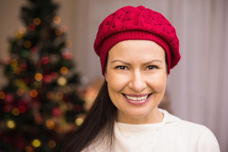 Portrait of a smiling brunette in red hat at home in the living room photo