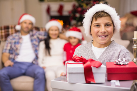 Festive son holding pile of gifts with his family behind  at home in the photo