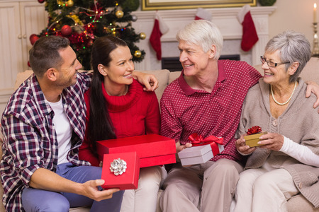 Smiling family holding present on sofa at home in the living room photo