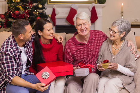 Smiling family holding gift on sofa at home in the living room photo