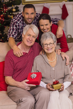 Happy family posing with presents at home in the living room photo