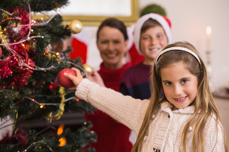 Smiling little girl decorating the christmas tree at home in the living room photo