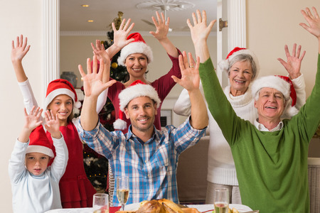 Happy extended family in santa hat cheering at camera at home in the living room photo