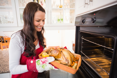 Smiling woman taking out her roast turkey at home in the kitchen Stock Photo