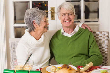 senior citizen: Portrait of a happy senior couple hugging at home in the living room Stock Photo