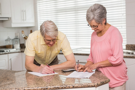 credit crunch: Senior couple paying their bills at home in the kitchen