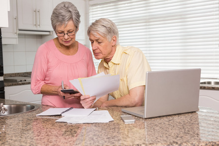 Senior couple paying their bills with laptop at home in the kitchen photo