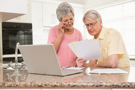 seniors: Senior couple paying their bills with laptop at home in the kitchen
