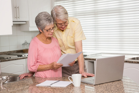 senior citizen: Senior couple paying their bills with laptop at home in the kitchen