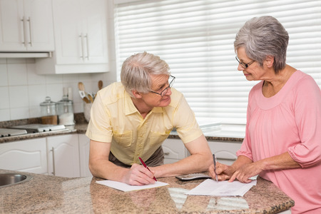 figuring: Senior couple paying their bills at home in the kitchen