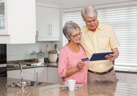 Senior couple shopping online with tablet pc at home in the kitchen photo