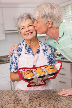 hot kiss: Senior man giving his wife a kiss at home in the kitchen