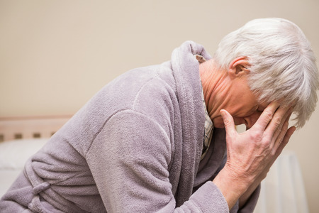 Senior man getting a headache at home in bedroom Stock Photo