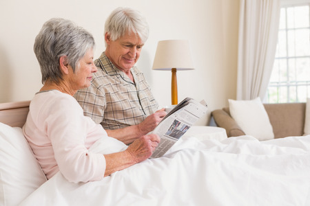 Senior couple relaxing in bed at home in bedroom photo