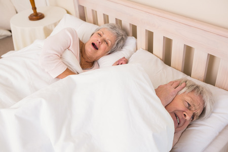 Senior man blocking out his wifes snoring at home in bedroom photo