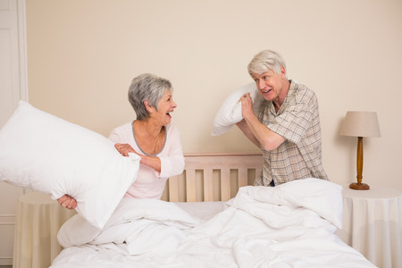 Senior couple having a pillow fight at home in the bedroom photo