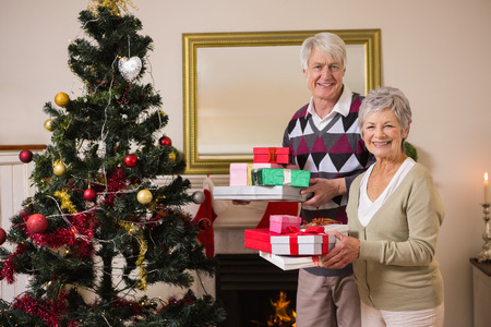 swapping: Senior couple swapping gifts by their christmas tree at home in the living room